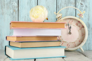 Books with clock on wooden background
