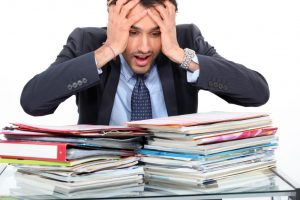 white male teacher adult suit stressed angry lots of paper piles of work